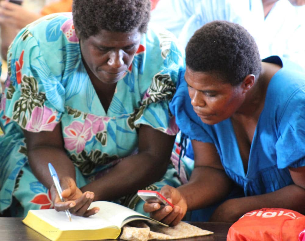 May, 2016: Women of the Paama language group in Vanuatu listen to a MegaVoice player while following the text in their newly dedicated print volume of the New Testament