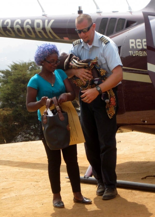 After helping the child's mother out of the helicopter, pilot Mark Spangler cradles his young passenger.