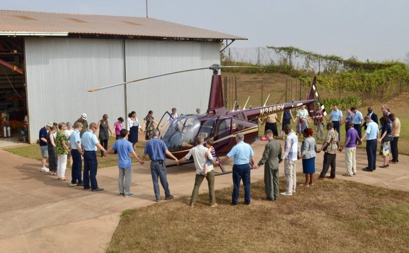 Staff gather for a prayer of dedication of the R66 before the pilots take off to head to home base in the mountains.