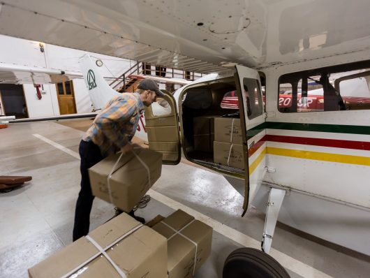 Brandon Penkoff loads a Cessna 206 with 14 boxes of Hdi New Testaments. Each box holds 45 copies, 672 total New Testaments.